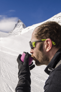 man drinking coffee in mountains